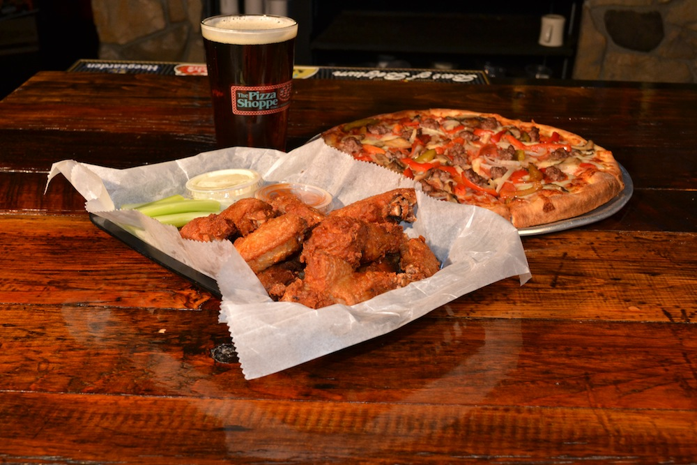This Is A Picture Of Buffalo Wings, A Beer, And A Pizza.